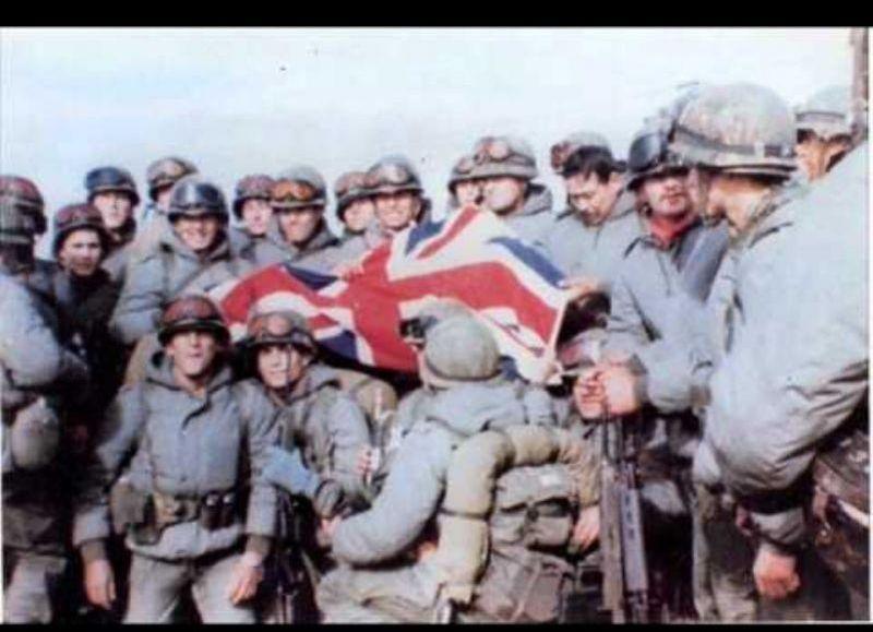 Soldados argentinos con bandera británica como trofeo de guerra.