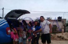 Facundo Alfonsín, junto a los chicos, repartiendo útiles desde el móvil de NOVA.